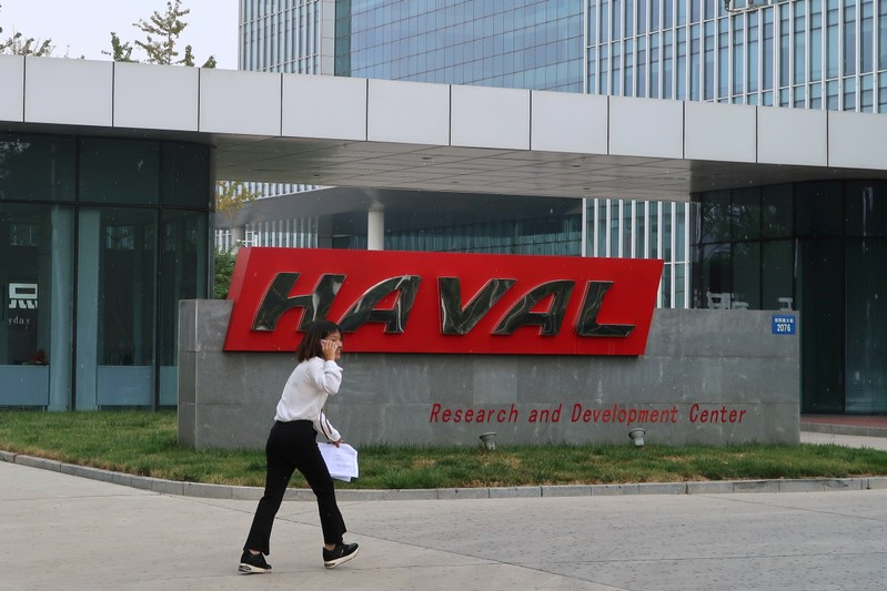 FILE PHOTO: A woman talks on her phone as she walks past a sign of Great Wall's HAVAL at its research and development center in Baoding, Hebei