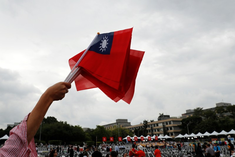 An audience waves Taiwanese flags during the National Day celebrations in Taipei