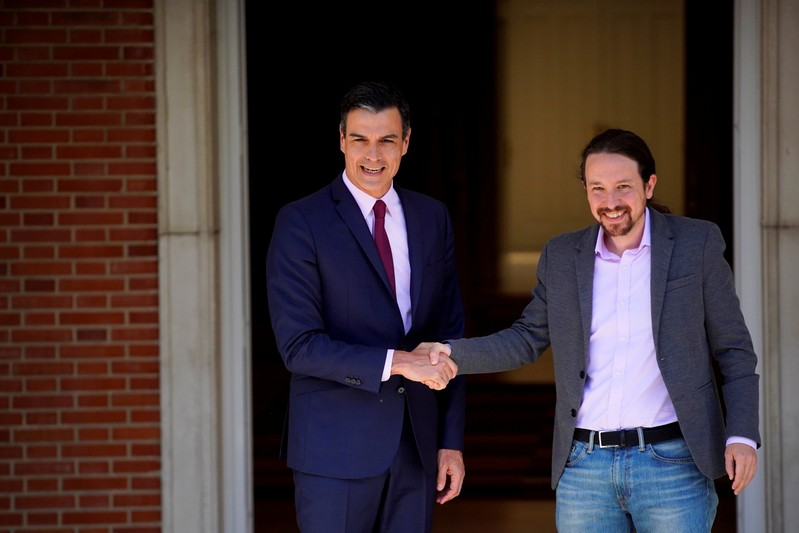 FILE PHOTO: Spain's acting Prime Minister Pedro Sanchez greets Unidas Podemos' (Together We Can) leader Pablo Iglesias at the Moncloa Palace in Madrid