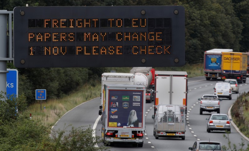 Vehicles pass beneath a sign warning of possible changes to freight procedures following Brexit on the M56 motorway near Chester, Britain