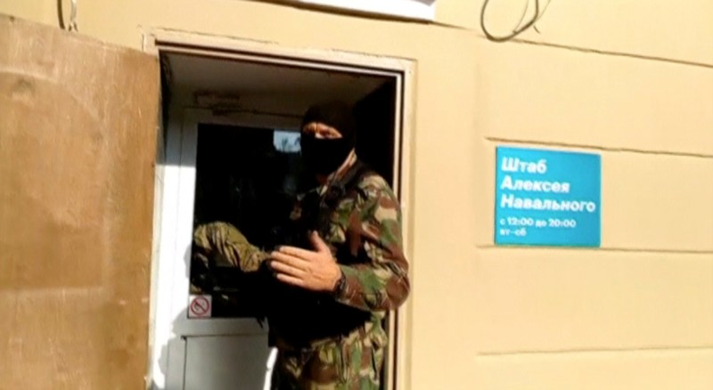 A still image shows a masked law enforcement officer during a raid in an office of Kremlin critic Navalny in Perm