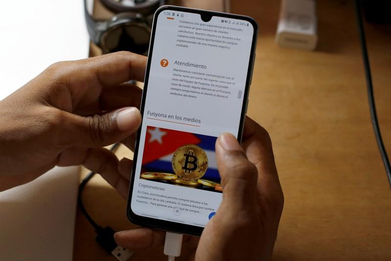 Jason Sanchez shows the startup Fusyona displayed on his mobile phone, Havana