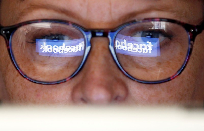 The Facebook logo is reflected on a woman's glasses in this photo illustration