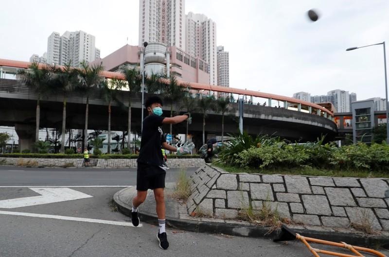 A demonstrator throws a stone in Tin Shui Wai in Hong Kong