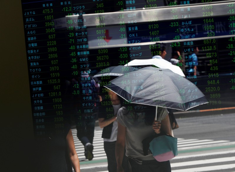 FILE PHOTO -  Passersby are reflected on a stock quotation board outside a brokerage in Tokyo