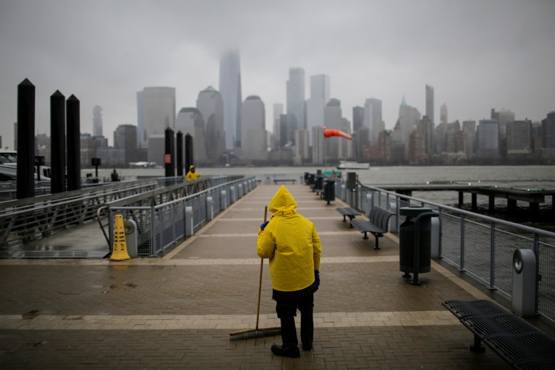 A ferry worker cleans the path for commuters during light snowfall while the New York skyline and the One World Trade Center are seen from Exchange Place