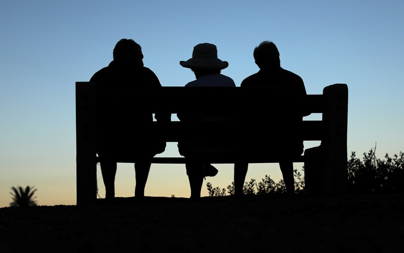 FILE PHOTO: Elderly people sit on a park bench after sun set in Encinitas