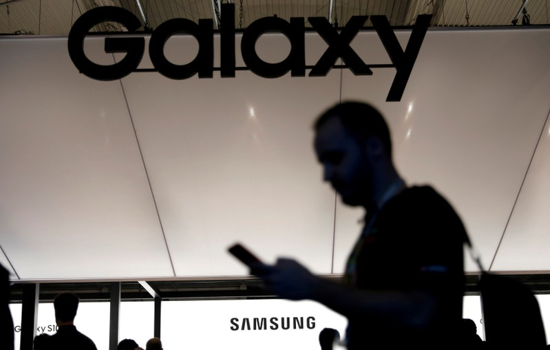 FILE PHOTO: A visitor uses a mobile phone at the Samsung booth at the Mobile World Congress in Barcelona