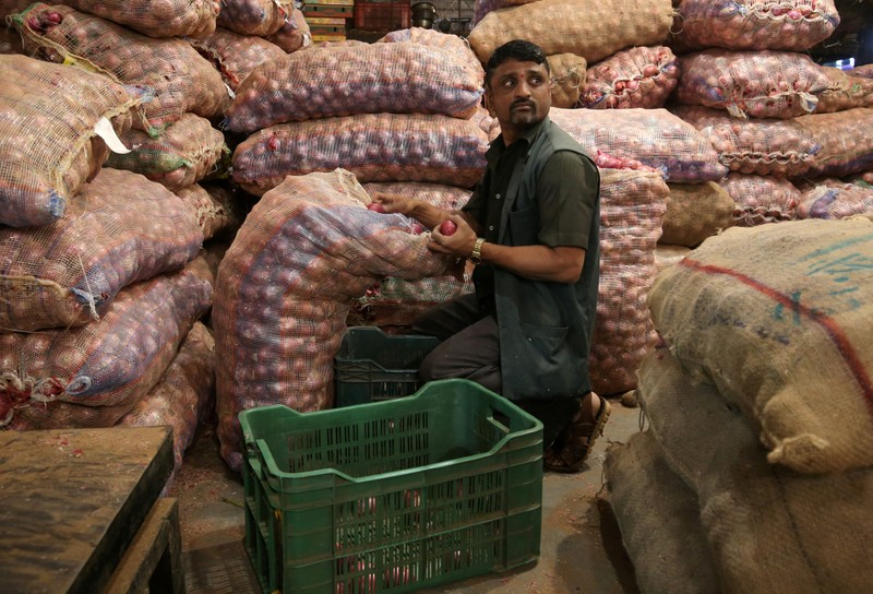 FILE PHOTO:  A man sorts onions at a vegetable wholesale market in Mumbai