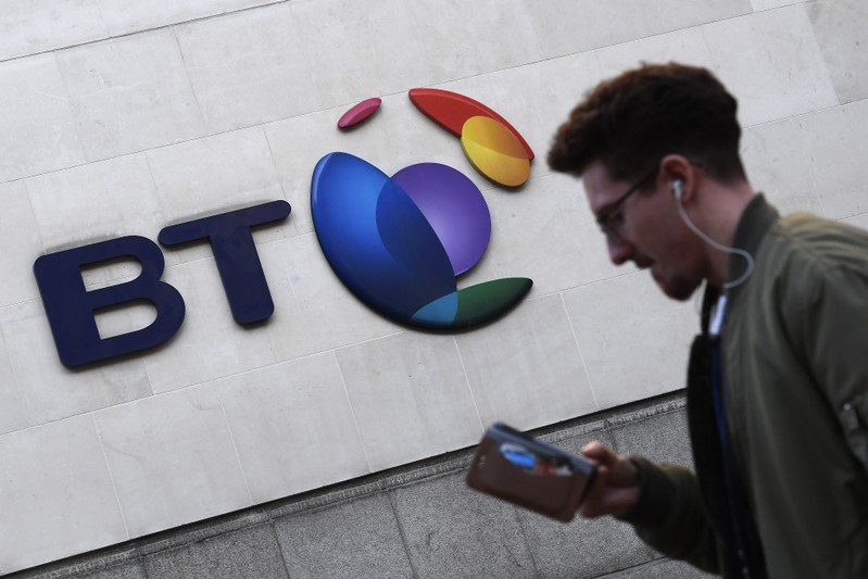 FILE PHOTO: A man walks past a BT logo outside of offices in the City of London