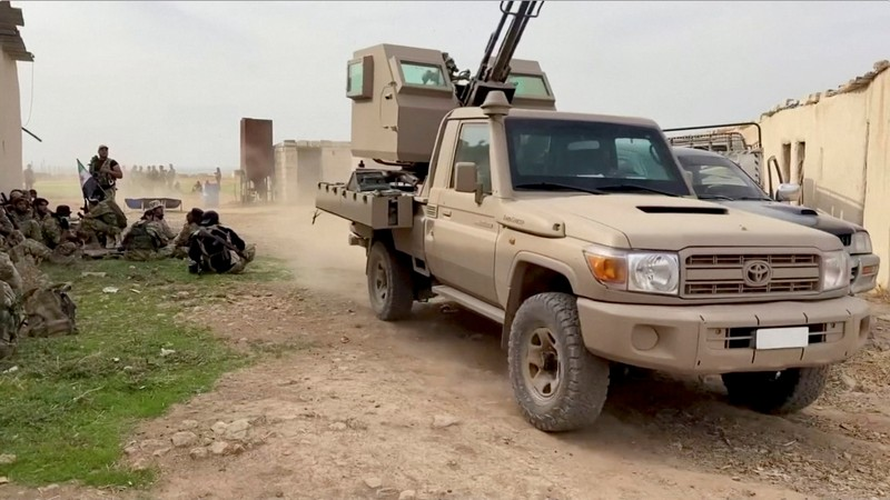 Still image from video shows a military vehicle driving past Syrian rebel fighters near Tal Abyad