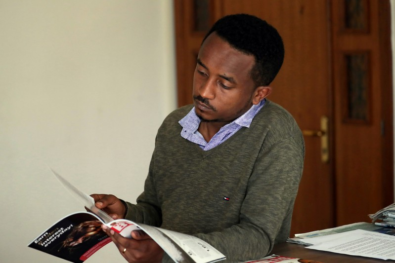Ethiopian Berhane reads news magazine with cover photo of Ethiopian PM in Addis Ababa