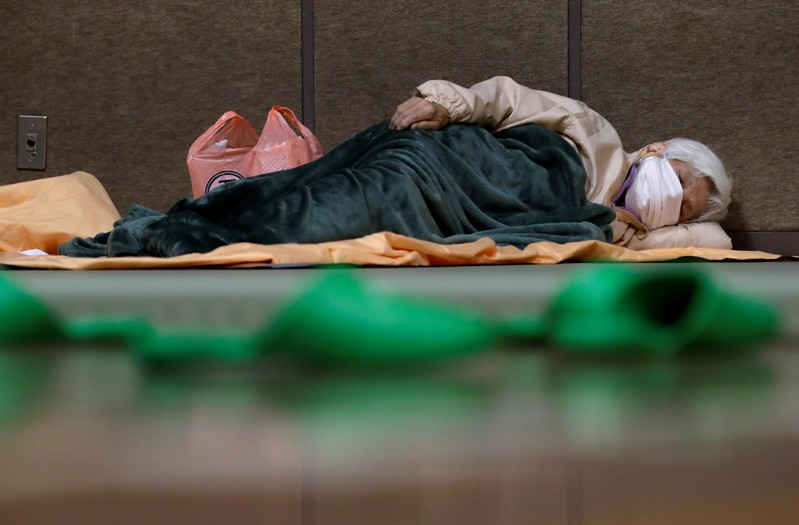 A woman sleeps in the evacuation centre for affected by the flood after Typhoon Hagibis in Nagano