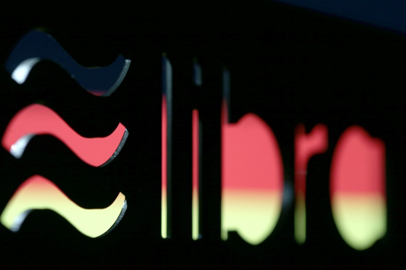 A 3D-printed Facebook Libra cryptocurrency logo is seen in front of displayed German flag in this illustration taken