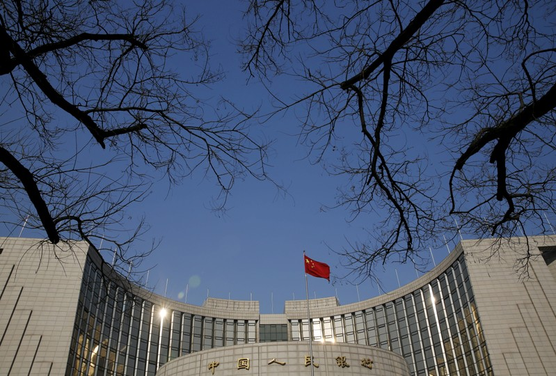 FILE PHOTO: A Chinese national flag flies at the headquarters of the People's Bank of China, the country's central bank, in Beijing