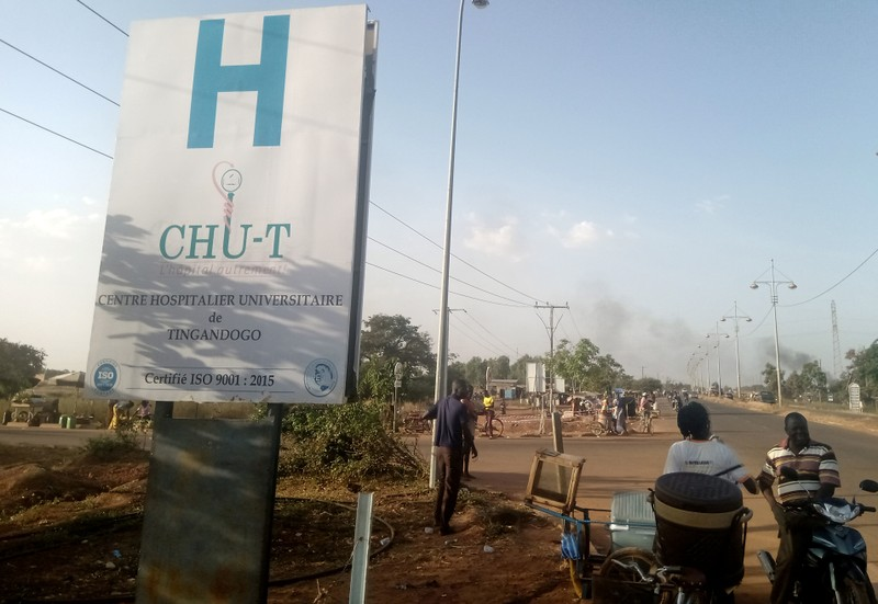 People are seen near a hospital in Ouagadougou, where some of the wounded were taken for treatment after an ambush on workers near a Canadian-owned mine