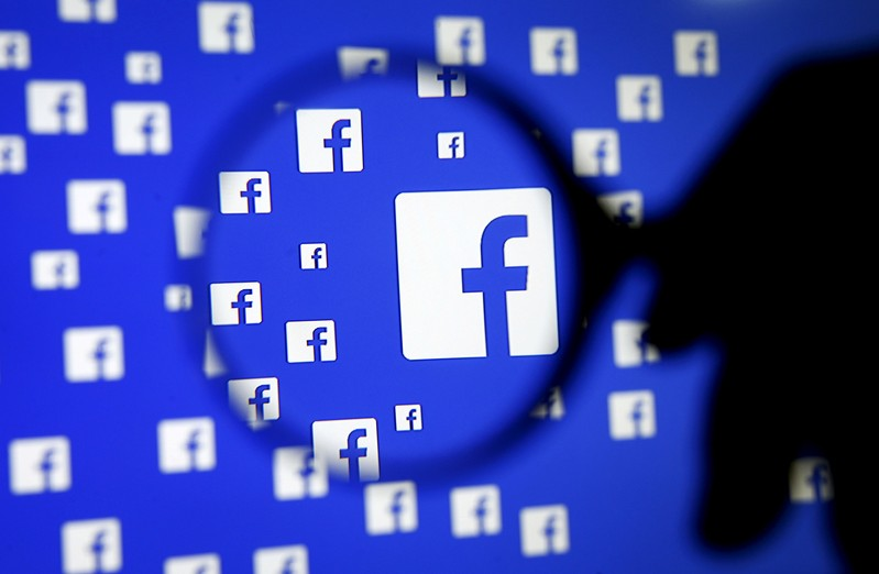 FILE PHOTO: A man poses with a magnifier in front of a Facebook logo on display in this illustration taken in Sarajevo