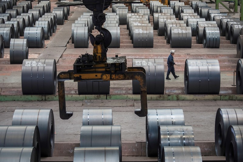 FILE PHOTO: Worker walks past steel rolls at the Chongqing Iron and Steel plant in Changshou