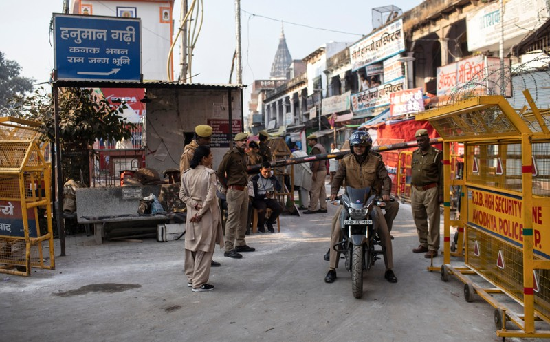 Police officers stand guard at a security barricade near a temple after Supreme Court's verdict on a disputed religious site, in Ayodhya