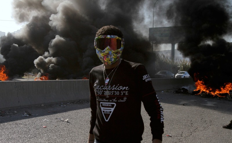 A demonstrator stands near burning tires during ongoing anti-government protests in Tripoli