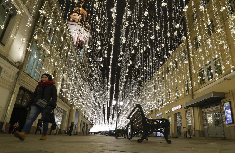FILE PHOTO:  A pedestrian walks along a street, decorated with festive illumination lights prior to the New Year and Christmas holidays, in central Moscow