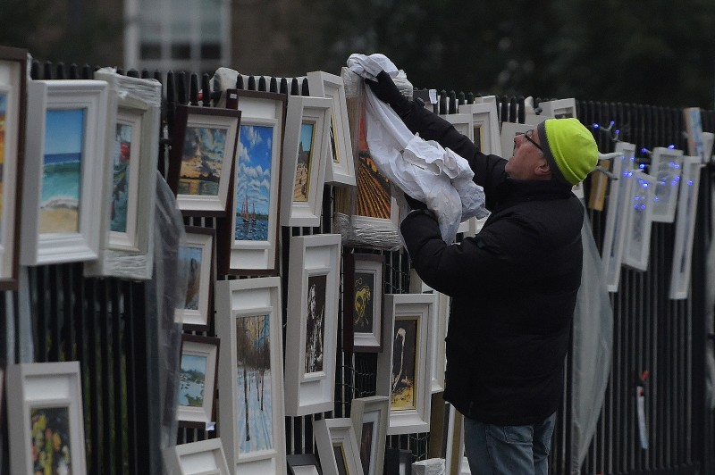 A street vendor dries rain off artworks he is selling on the streets in Dublin