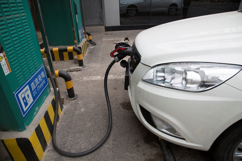 Charging cable is seen hooked to a car at a charging point for electric vehicles in Beijing