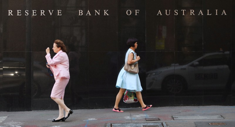 Two women walk next to the Reserve Bank of Australia headquarters in central Sydney