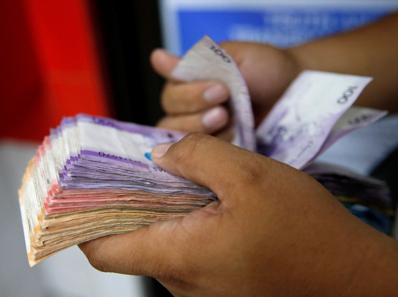 Man counts wad of Philippine Peso bills in Makati