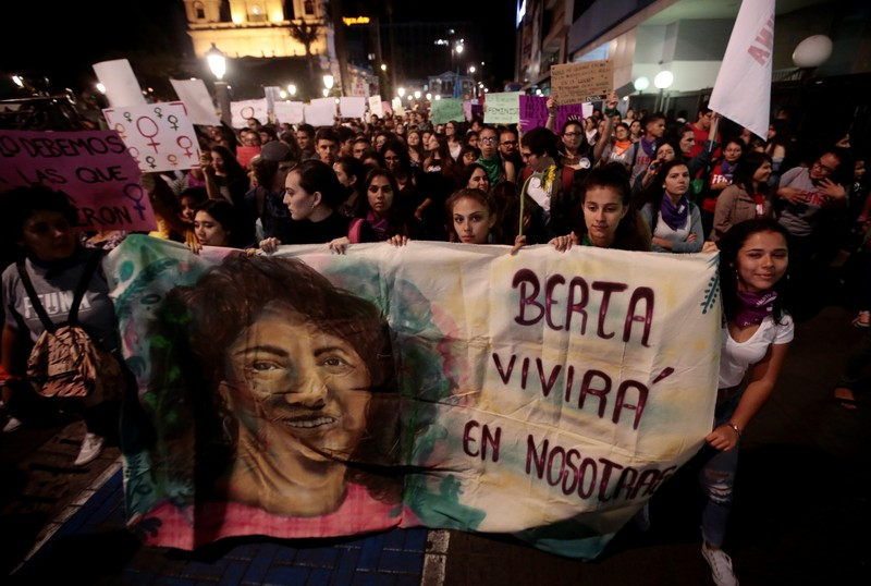 Women display a banner at a march during International Women's Day in San Jose