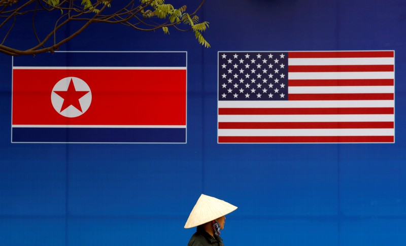 A person walks past a banner showing North Korean and U.S. flags ahead of the North Korea-U.S. summit in Hanoi