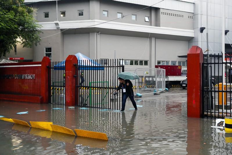 A man walks on the flooded entrance of the Rizal Memorial Stadium after Typhoon Kammuri hit Metro Manila
