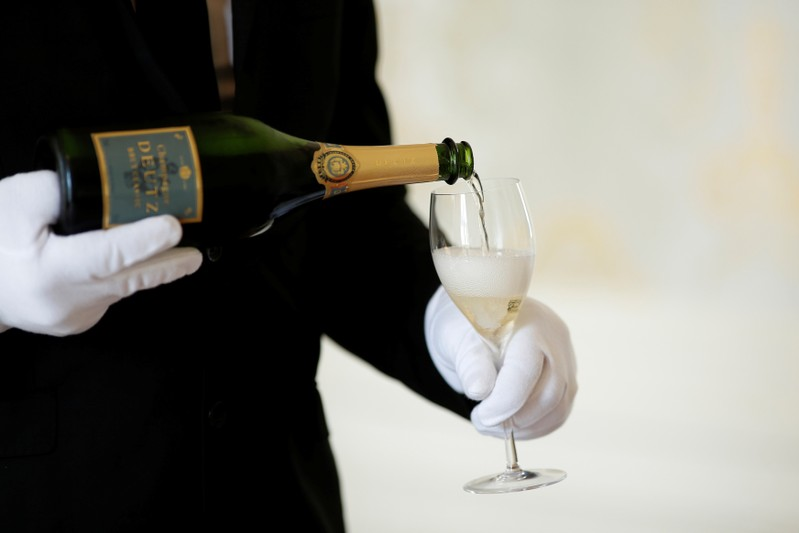 FILE PHOTO: An employee serves a glass of Champagne during the traditional wine harvest at the Champagne house Deutz in Ay