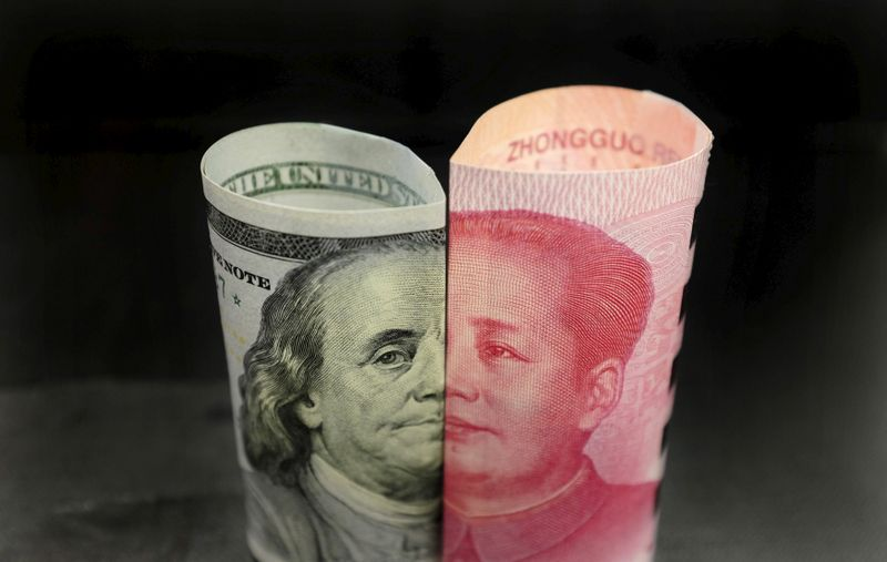FILE PHOTO: A Benjamin Franklin U.S. 100 dollar banknote and a Chinese 100 yuan banknote with late Chinese Chairman Mao Zedong are seen in this picture illustration in Beijing, China