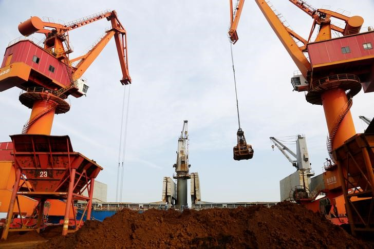 Cranes unload imported iron ore from a cargo vessel at a port in Lianyungang, Jiangsu