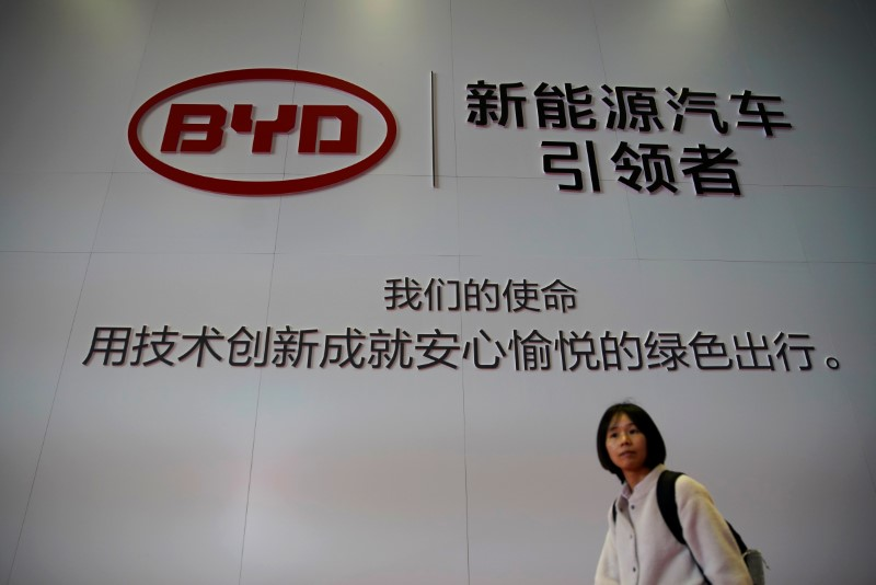 Woman walks past a BYD sign at the second media day for the Shanghai auto show in Shanghai