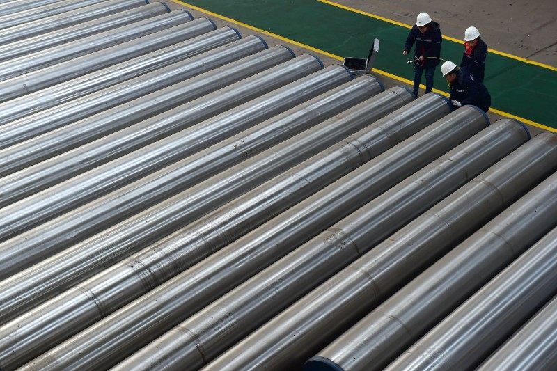 Workers check on seamless steel pipes at a factory of a steel products manufacturer in Cangzhou, Hebei