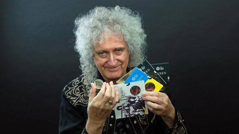 Guitarist Brian May of band Queen poses with a 5-pound coin