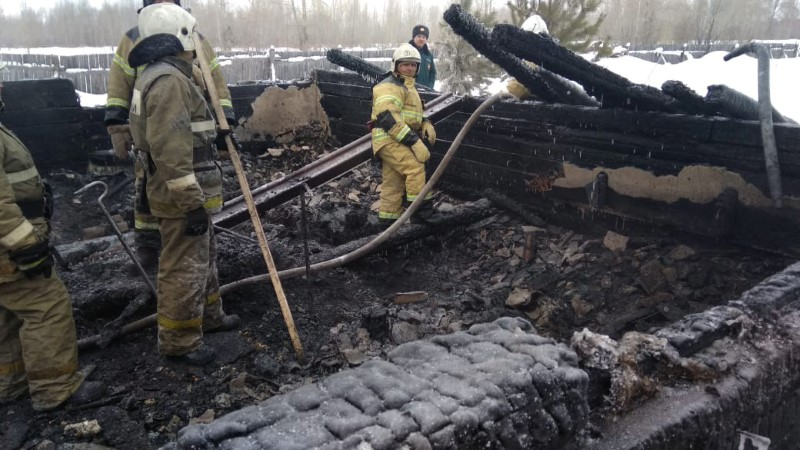 Russian Emergencies Ministry members work at the site of a fire in Tomsk region