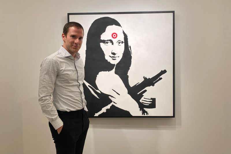 Scott Lynn, CEO and founder of Masterworks, poses next to a Banksy artwork in New York