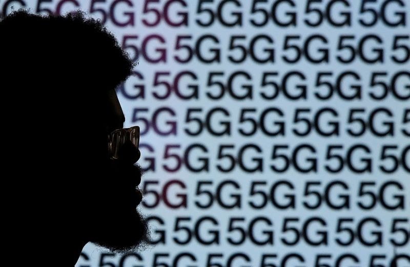 FILE PHOTO: A man walks past an advertisement promoting the 5G data network at a mobile phone store in London