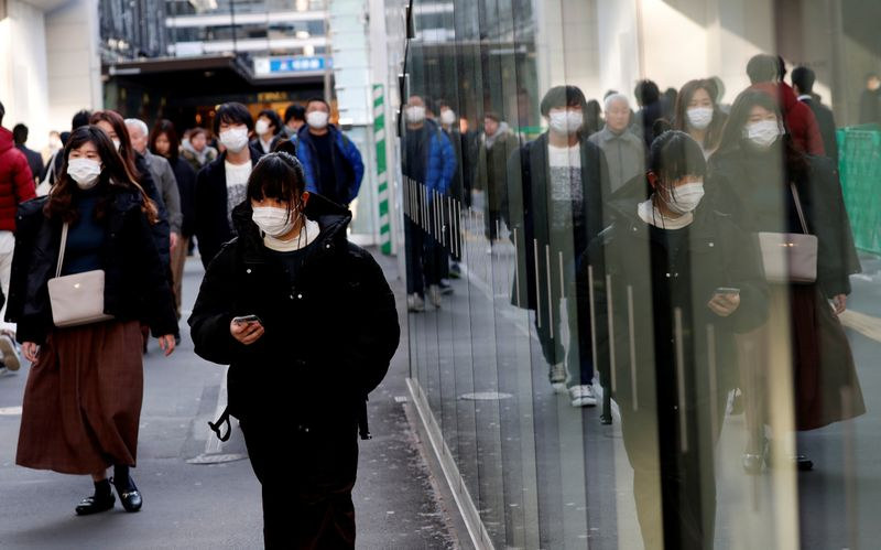 Pedestrians wearing surgical masks make their way in front of Yokohama station in Yokohama