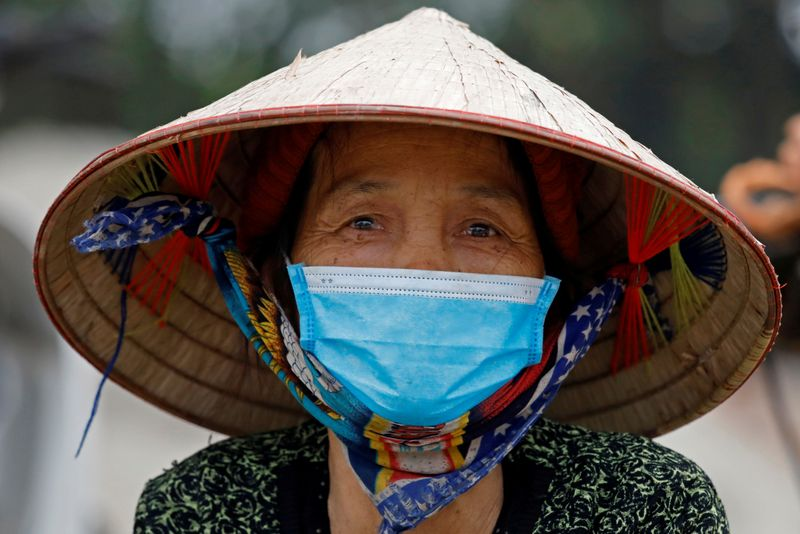 A woman wearing a protective mask walks in a village in Vinh Phuc province