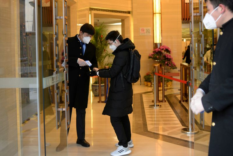 FILE PHOTO: Jin Yang, 28, who works in a department of China's State Administration of Foreign Exchange, has his temperature checked at an entrance to his office, in the morning on his first day of returning to work after the extended Lunar New Year holida