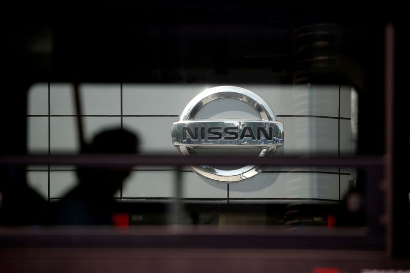 The logo of Nissan is seen through a window of a bus passing by its dealership in Seoul