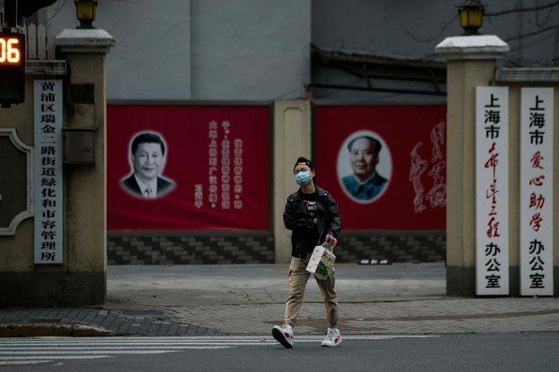 A man wearing a mask walks by portraits of Chinese President Xi Jinping and late Chinese chairman Mao Zedong as the country is hit by an outbreak of the novel coronavirus, on a street in Shanghai