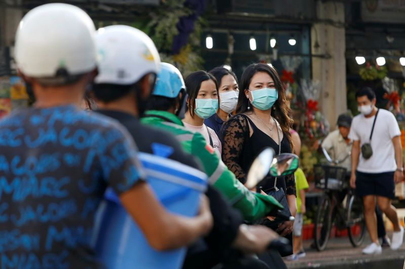 People drive motorbikes near pedestrians wearing face masks in Ho Chi Minh