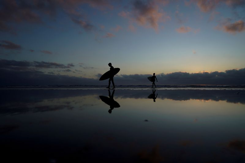 FILE PHOTO: A father and his son make their way in from surfing at Cardiff State Beach in Encinitas