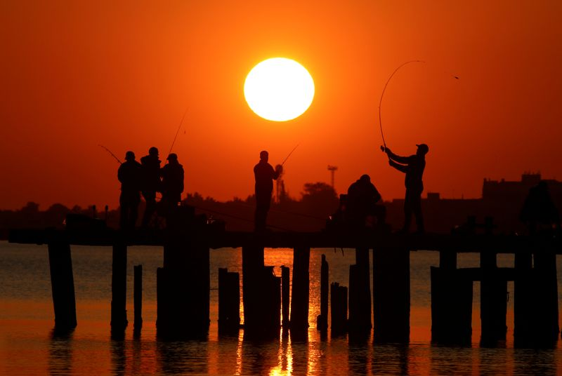 FILE PHOTO: People fish at sunset in Yevpatoriya