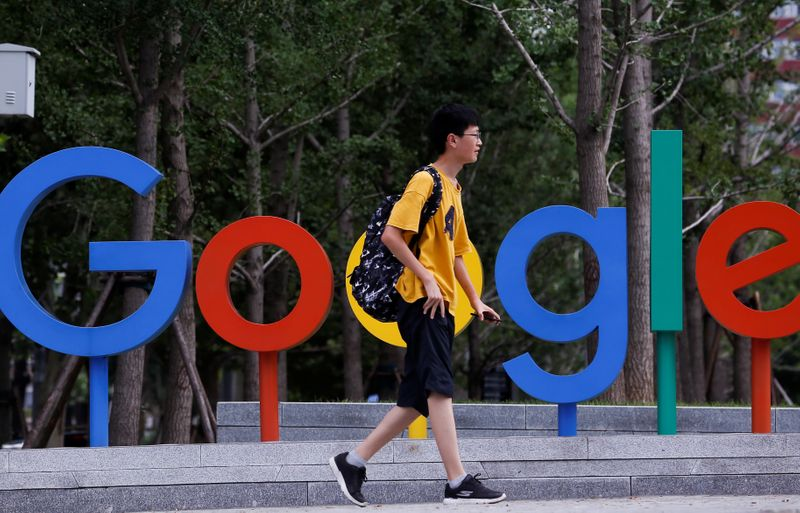 A man walks past the brand logo of Alphabet Inc's Google outside its office in Beijing